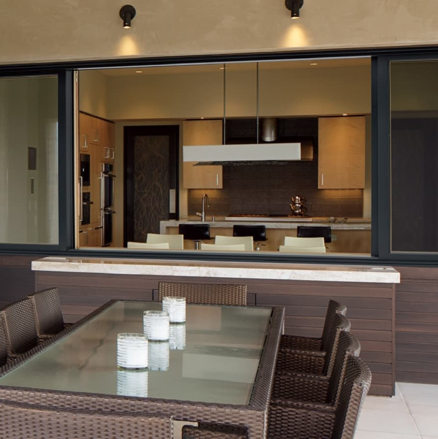 Exterior photo of large glider window that looks into the kitchen from the patio