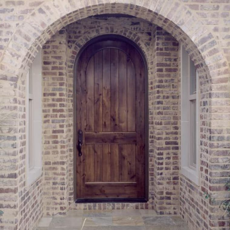 Wooden entrance door on brick home