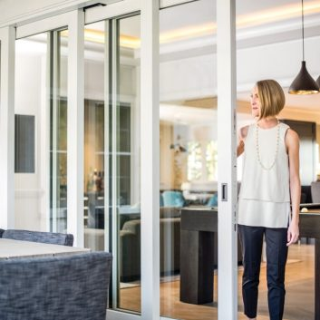 Large, sliding scenic door being opened by homeowner